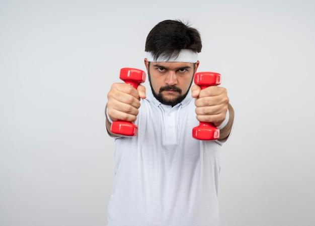 Przekonany, młody człowiek sportowy, noszenie opaski i opaski, ćwiczenia z hantlami na białym tle na białej ścianie