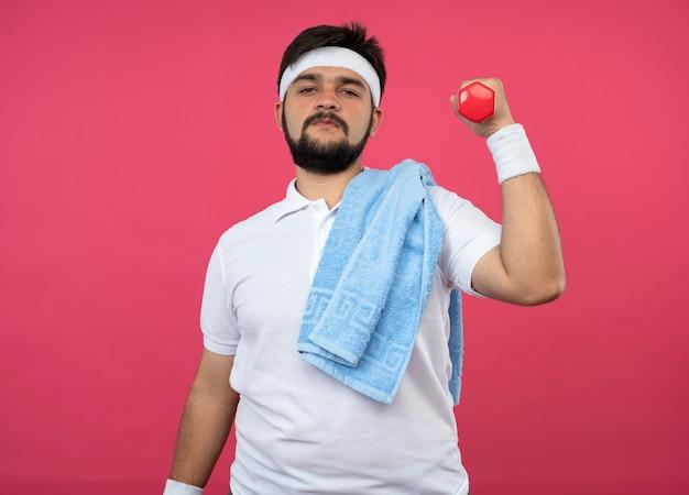 Przekonany, młody człowiek sportowy, noszenie opaski i opaski, ćwiczenia z hantlami z ręcznikiem na ramieniu