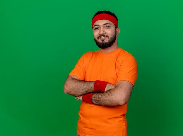 Przekonany, młody człowiek sportowy, noszenie opaski i opaski na rękę, skrzyżowanie rąk na białym tle na zielonym tle z miejsca na kopię