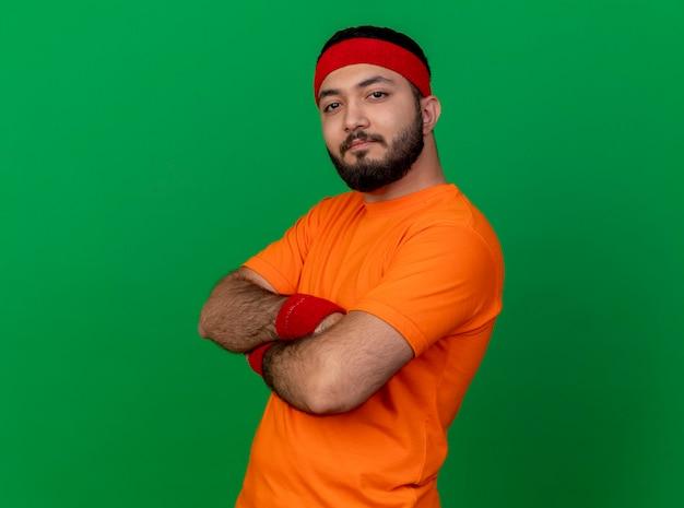 Przekonany, młody człowiek sportowy, noszenie opaski i opaski na rękę, skrzyżowanie rąk na białym tle na zielonym tle