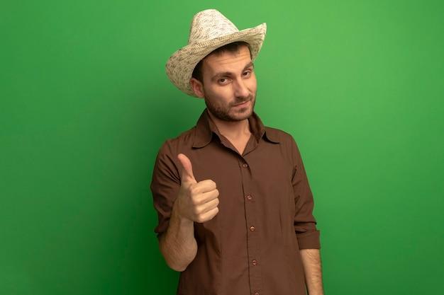 Przekonany, młody człowiek w kapeluszu plażowym, patrząc z przodu pokazując kciuk do góry na białym tle na zielonej ścianie