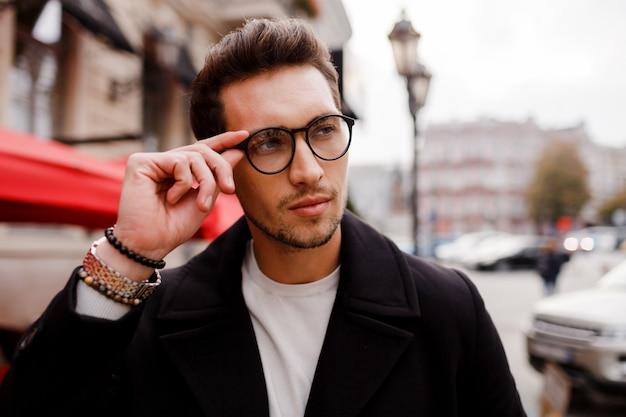 Przekonany, młody człowiek w pełnym garniturze, odwracając wzrok stojąc na zewnątrz w europejskim mieście. noszenie okularów. stylowa fryzjerka.