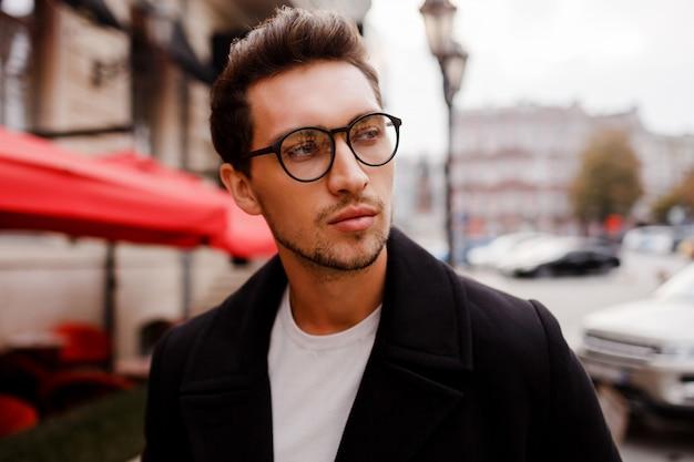 Przekonany, młody człowiek w pełnym garniturze, odwracając wzrok stojąc na zewnątrz w europejskim mieście. noszenie okularów.