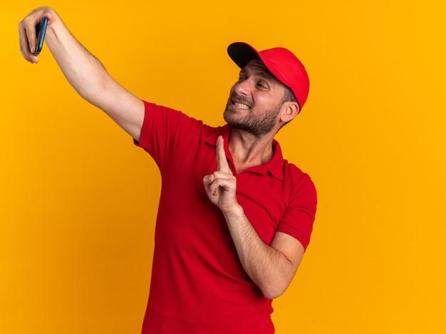 Przekonany młody kaukaski mężczyzna dostawy w czerwonym mundurze i czapce robi znak pokoju pokazujący zęby biorąc selfie na białym tle na pomarańczowej ścianie z miejscem na kopię