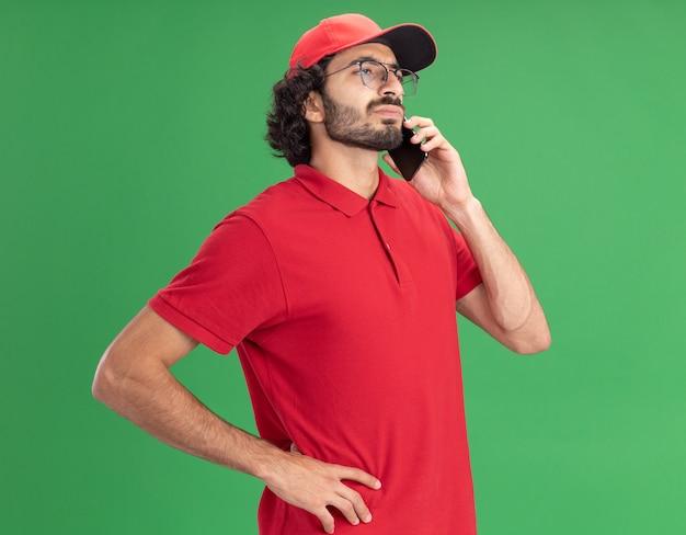 Przekonany młody kaukaski mężczyzna dostawy w czerwonym mundurze i czapce w okularach, trzymając rękę na talii, rozmawiając przez telefon, patrząc prosto na zieloną ścianę