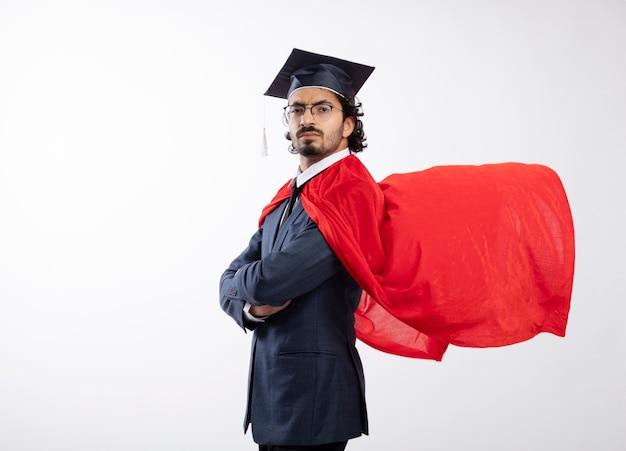 Przekonany, młody kaukaski mężczyzna superbohatera w okularach optycznych, ubrany w garnitur z czerwonym płaszczem i czapką ukończenia szkoły, stoi bokiem