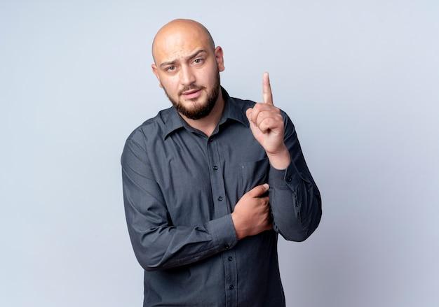 Przekonany, młody łysy mężczyzna call center kładąc rękę na klatce piersiowej i podnosząc palec na białym tle na biały z miejsca na kopię