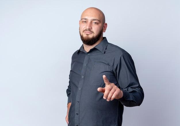 Przekonany, młody łysy mężczyzna call center kładąc rękę na talii i wskazując na białym tle na biały z miejsca na kopię