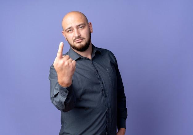 Przekonany, młody łysy mężczyzna call center pokazując jeden z ręką na białym tle na fioletowo z miejsca na kopię