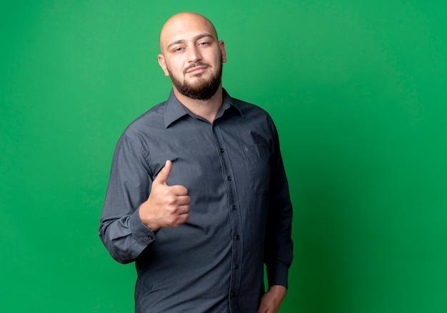 Przekonany, młody łysy mężczyzna call center pokazując kciuk do góry na białym tle na zielono z miejsca na kopię