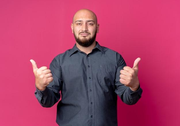Przekonany, młody łysy mężczyzna call center pokazując kciuki do góry na białym tle na karmazynowy