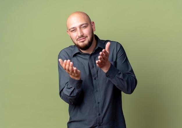 Przekonany, młody łysy mężczyzna call center pokazując puste dłonie odizolowane na oliwkowej zieleni z miejsca na kopię