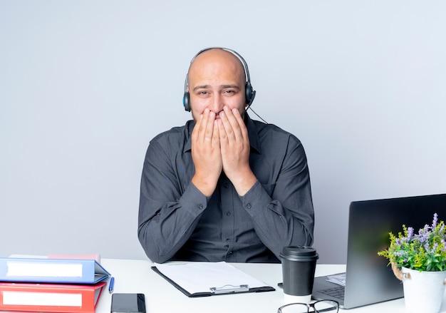 Przekonany, młody łysy mężczyzna call center sobie zestaw słuchawkowy siedzi przy biurku z narzędzi pracy kładąc ręce na ustach na białym tle