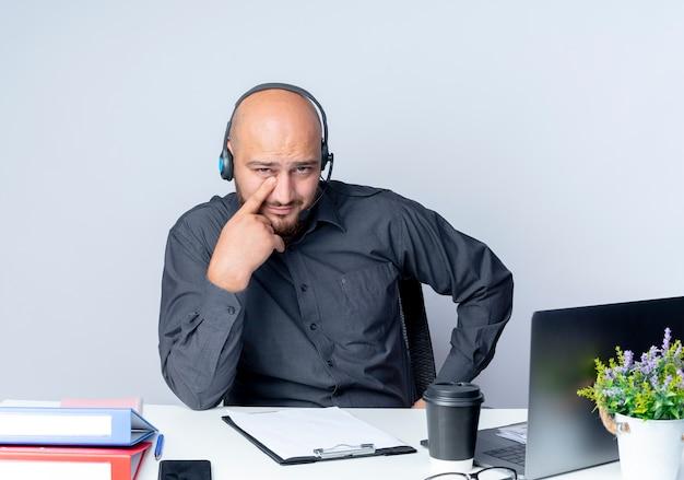 Przekonany, młody łysy mężczyzna call center sobie zestaw słuchawkowy siedzi przy biurku z narzędzi pracy oddanie palca pod oko na białym tle