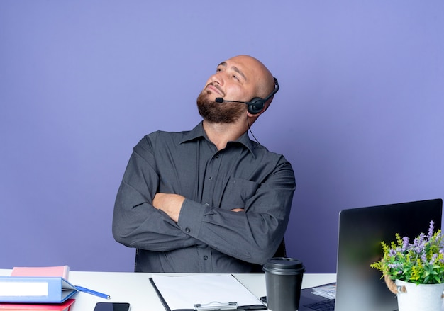 Przekonany, młody łysy mężczyzna call center sobie zestaw słuchawkowy siedzi z zamkniętą postawą przy biurku z narzędzi pracy patrząc w górę na białym tle na fioletowo