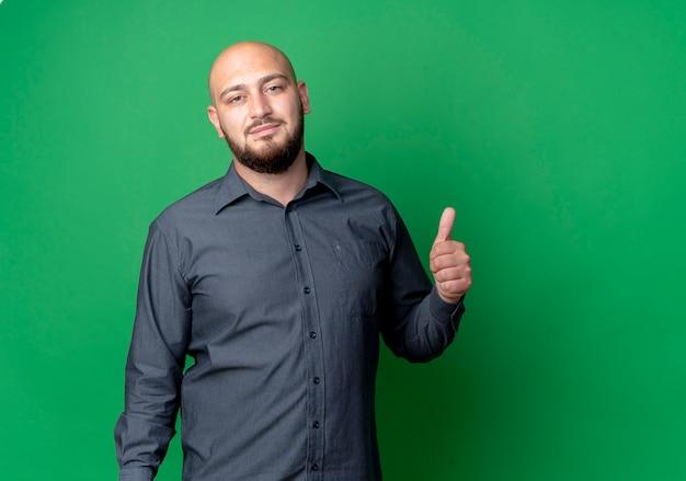 Przekonany, młody łysy mężczyzna call center szuka i pokazuje kciuk w górę na białym tle na zielono z miejsca na kopię
