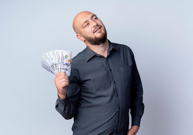 Przekonany, młody łysy mężczyzna call center trzyma pieniądze patrząc na białym tle na biały z miejsca na kopię