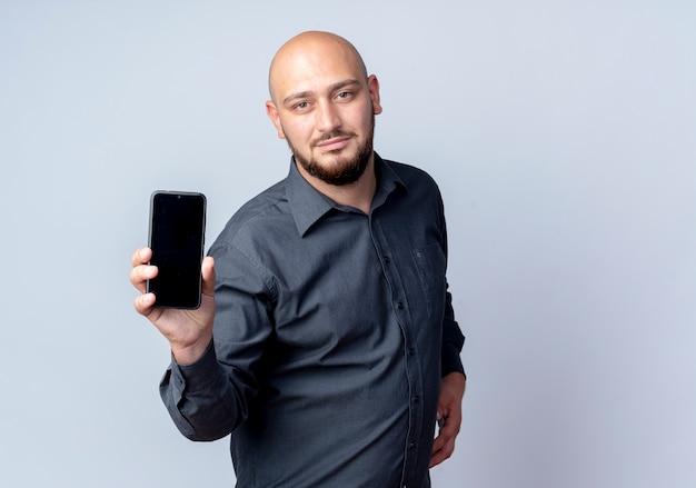 Przekonany, młody łysy mężczyzna call center wyciągając telefon komórkowy w kierunku kamery na białym tle na biały z miejsca na kopię