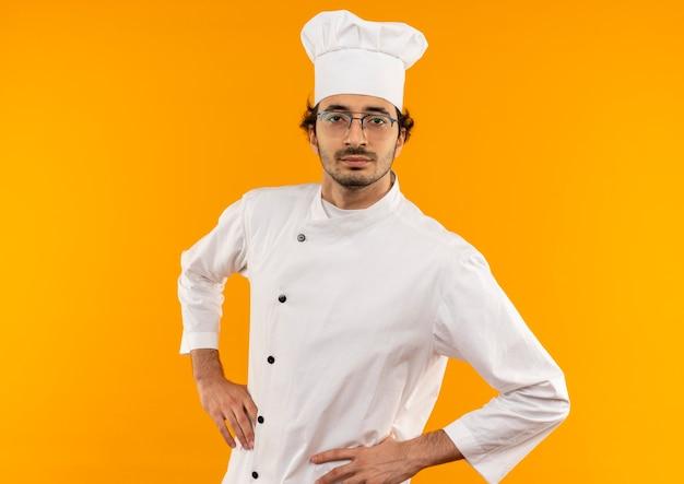 Przekonany, młody mężczyzna kucharz na sobie mundur szefa kuchni i okulary, kładąc ręce na biodrze