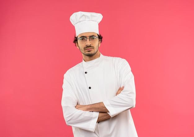 Przekonany, młody mężczyzna kucharz na sobie mundur szefa kuchni i okulary skrzyżowania rąk