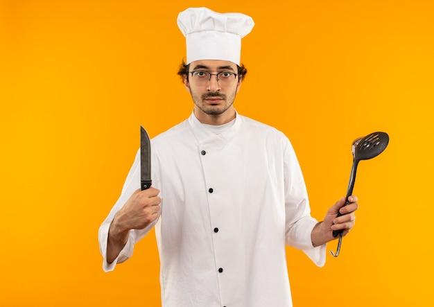 Przekonany, młody mężczyzna kucharz na sobie mundur szefa kuchni i okulary, trzymając łopatkę i nóż