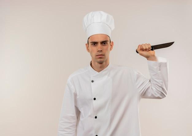 Przekonany, młody mężczyzna kucharz ubrany w mundur szefa kuchni trzymając nóż na na białym tle białej ściany z miejsca na kopię