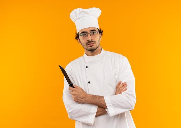 Przekonany, młody mężczyzna kucharz w mundurze szefa kuchni i okularach, skrzyżowaniu rąk i trzymając nóż