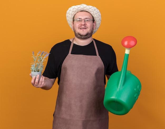 Przekonany, młody mężczyzna ogrodnik w kapeluszu ogrodniczym i rękawiczkach, trzymając konewkę z kwiatem w doniczce na białym tle na pomarańczowej ścianie