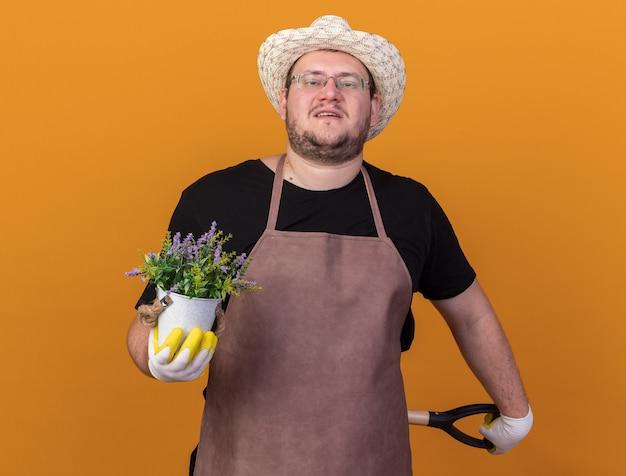 Przekonany, młody mężczyzna ogrodnik w kapeluszu ogrodniczym i rękawiczkach, trzymając łopatę za talią z kwiatem w doniczce na białym tle na pomarańczowej ścianie