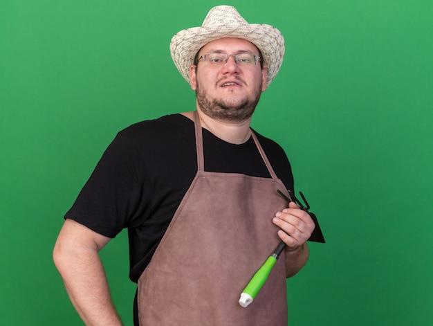 Przekonany, młody mężczyzna ogrodnik w kapeluszu ogrodniczym, trzymając motyka grabie, kładąc rękę na biodrze na zielonej ścianie z kopią przestrzeni