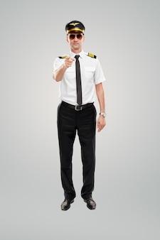 Przekonany, młody pilot płci męskiej, wskazując na aparat na szarym tle