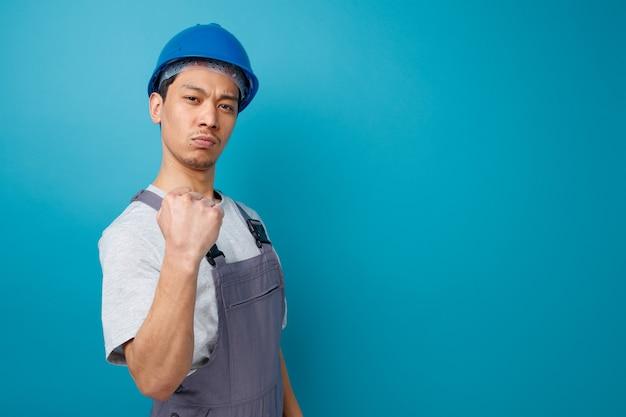 Przekonany, młody pracownik budowlany na sobie hełm ochronny i mundur stojący w widoku profilu robi tak gest