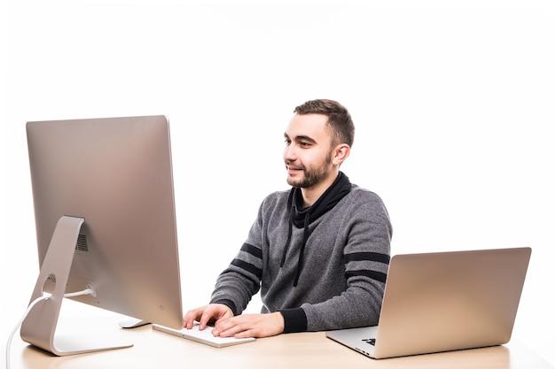 Przekonany, młody przedsiębiorca siedzi przy stole z laptopem i komputerem na białym tle
