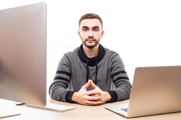 Przekonany, młody przedsiębiorca siedzi przy stole z laptopem i komputerem, patrząc na kamery na białym tle