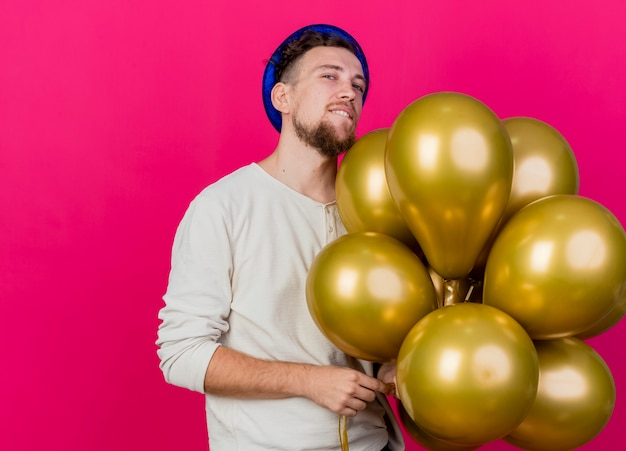 Przekonany, młody przystojny facet w kapeluszu, trzymając balony, patrząc na przednie gryzienie wargi na białym tle na szkarłatnej ścianie