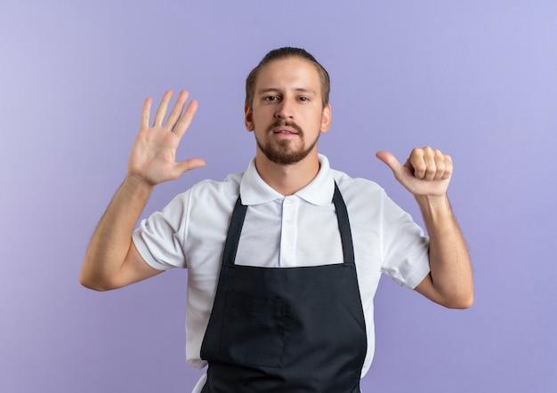 Przekonany, młody przystojny fryzjer na sobie mundur pokazujący sześć z rękami odizolowanymi na fioletowo
