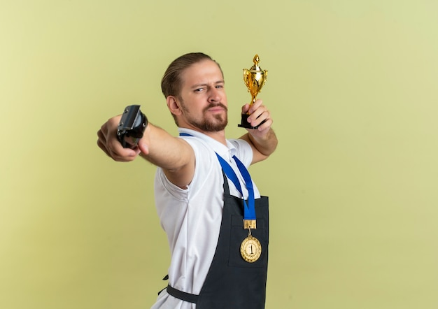 Przekonany, młody przystojny fryzjer noszący medal na szyi, wyciągając maszynkę do strzyżenia włosów i trzymając puchar zwycięzcy na białym tle na oliwkowej zieleni z miejsca na kopię