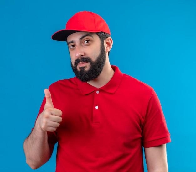 Przekonany, młody przystojny kaukaski mężczyzna dostawy ubrany w czerwony mundur i czapkę pokazując kciuk w górę na białym tle na niebiesko
