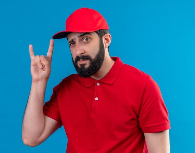 Przekonany, młody przystojny kaukaski mężczyzna dostawy ubrany w czerwony mundur i czapkę robi rockowy znak na niebieskim tle