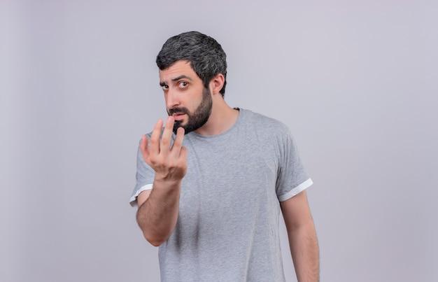 Przekonany, młody przystojny kaukaski mężczyzna robi tu gest i patrząc na białym tle na biały z miejsca na kopię