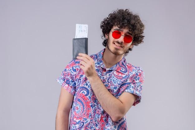 Przekonany, młody przystojny kędzierzawy podróżnik mężczyzna w okularach przeciwsłonecznych, trzymając portfel i bilety lotnicze i mrugając na odizolowanej białej przestrzeni z kopią miejsca