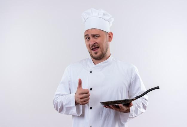 Przekonany młody przystojny kucharz w mundurze szefa kuchni trzymający patelnię pokazujący kciuk na białym tle na białej ścianie