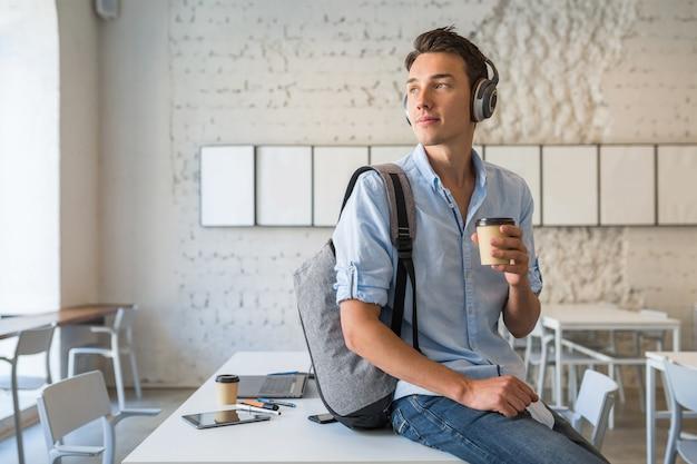 Przekonany, młody przystojny mężczyzna siedzi na stole w słuchawkach z plecakiem w biurze współpracującym, pije kawę