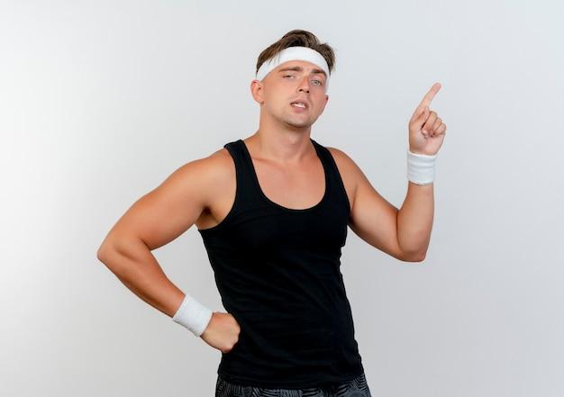 Przekonany, młody przystojny mężczyzna sportowy, noszenie opaski i opaski na rękę, kładąc rękę na talii i skierowaną w górę na białym tle