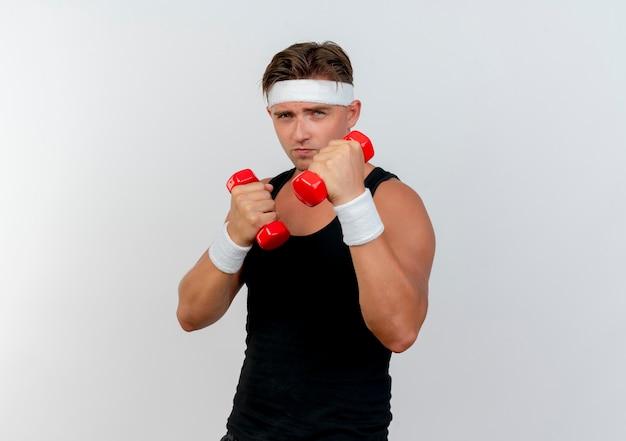 Przekonany, młody przystojny mężczyzna sportowy, noszenie opaski i opaski na rękę, trzymając hantle na białym tle biały z miejsca na kopię