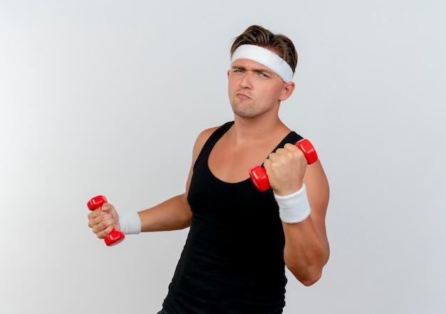 Przekonany, młody przystojny mężczyzna sportowy, noszenie opaski i opaski na rękę, trzymając hantle na białym tle