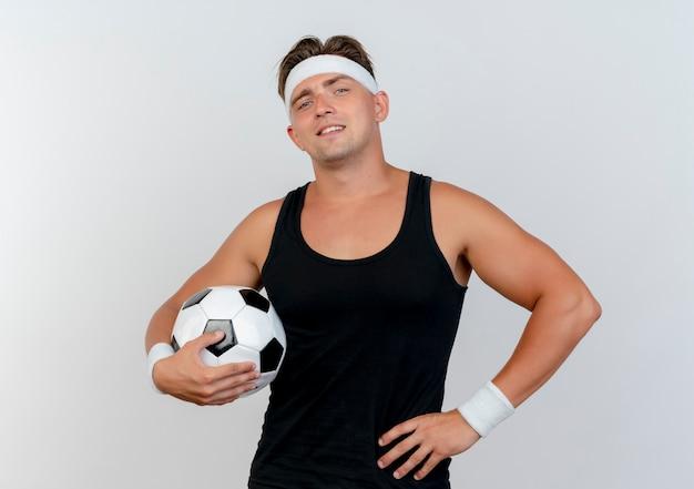 Przekonany, młody przystojny mężczyzna sportowy, noszenie opaski i opaski na rękę, trzymając piłkę nożną i kładąc rękę na talii na białym tle