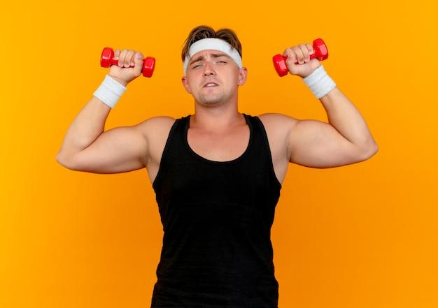 Przekonany, młody przystojny sportowy mężczyzna nosi opaskę i opaski na rękę podnosząc hantle na pomarańczowym tle
