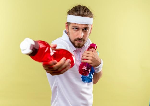 Przekonany, młody przystojny sportowy mężczyzna nosi opaskę i opaski, trzymając i rozciągając butelki z wodą izolowane na zielonej ścianie z kopią przestrzeni
