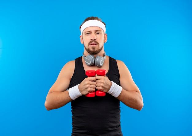 Przekonany, młody przystojny sportowy mężczyzna nosi opaskę, opaski i słuchawki na szyi, trzymając hantle izolowane na niebieskiej ścianie